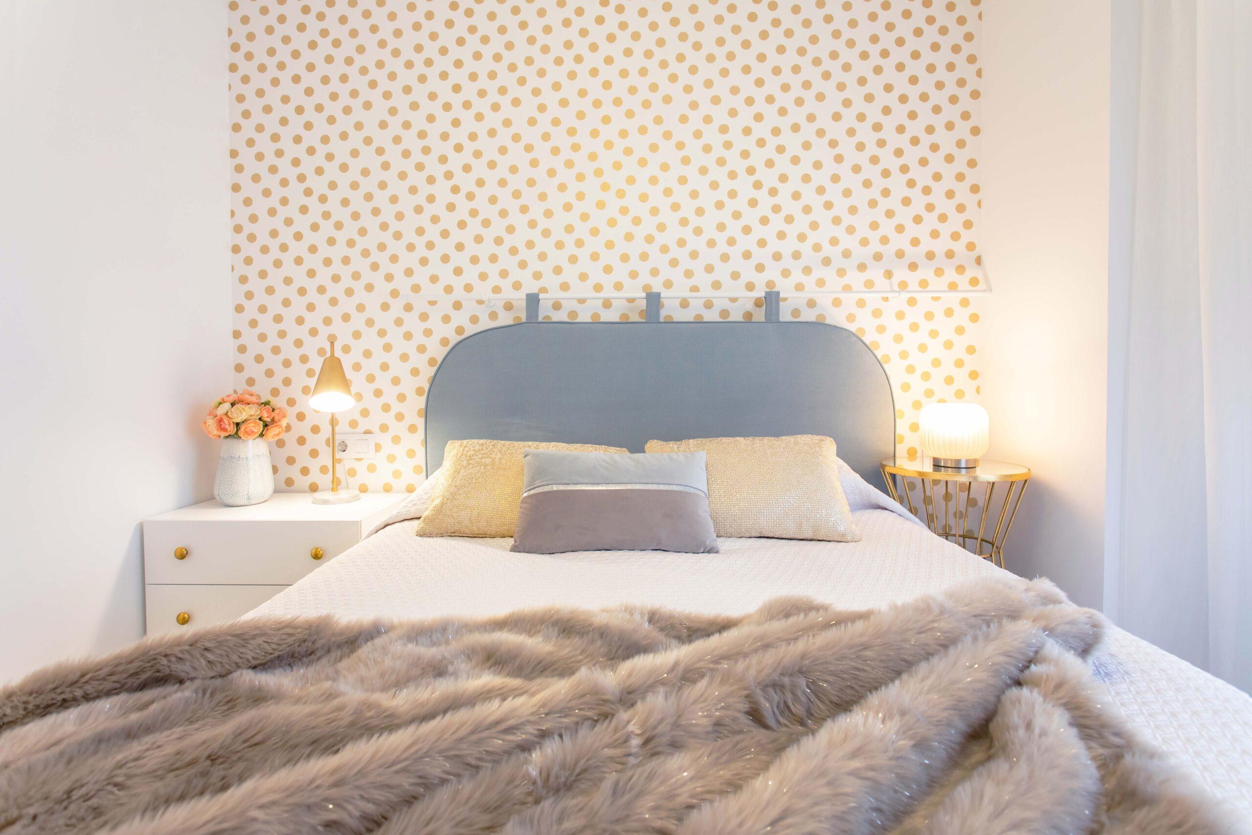 Dormitorio principal con papel decorativo de lunares dorado dando protagonismo al cabezal estilo hotel