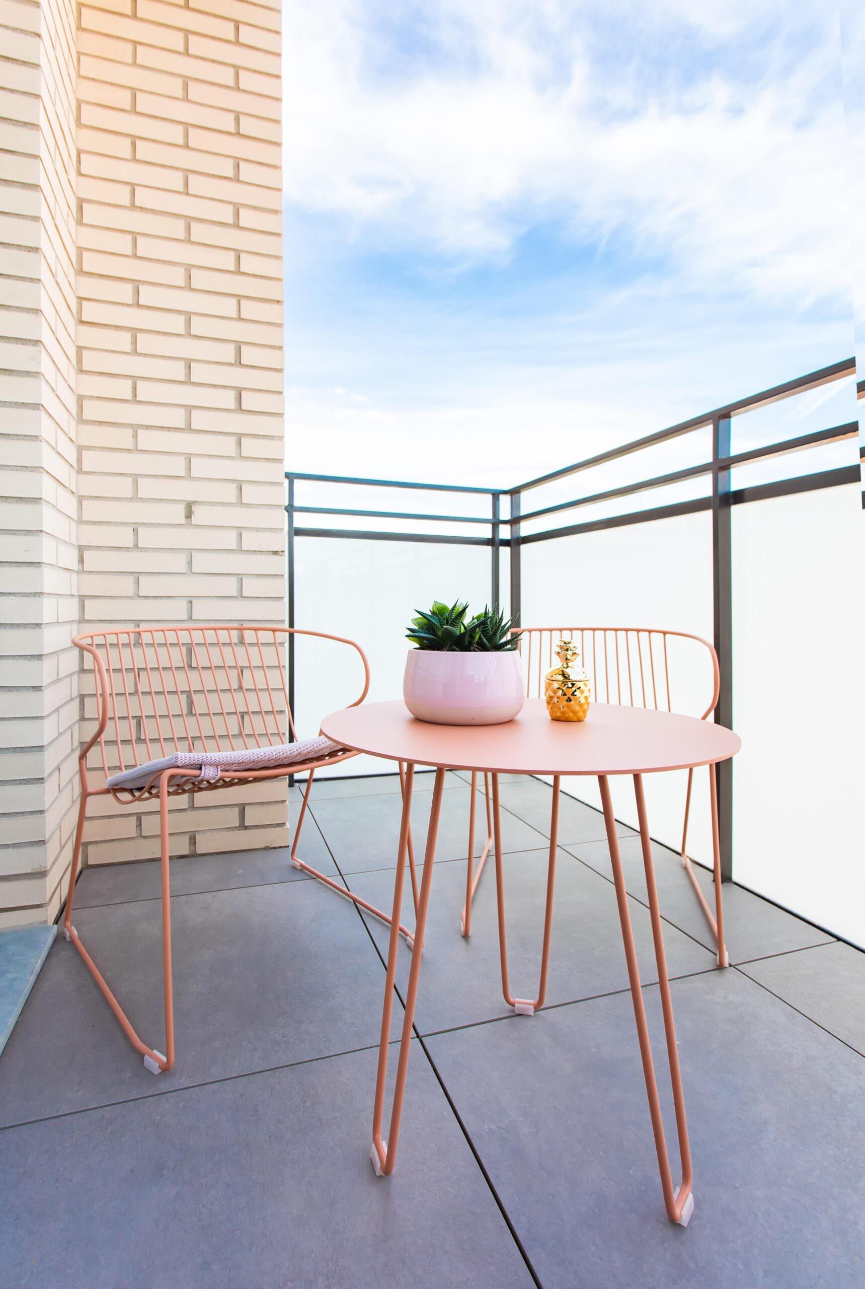 Pequeña terraza en el balcón con mobiliario en tonos de acorde al resto de la vivienda